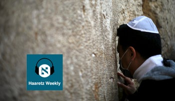 A man with a mask on his face prays at the Western Wall on Sunday Feb. 16, 2020, during a prayer session asking for divine intervention to help stave off coronavirus.