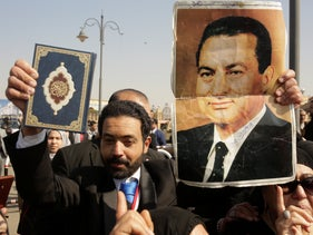 A supporter holds a photo of Egypt's ousted autocratic President Hosni Mubarak in one hand and a  Quran, the Muslim holy book, in the other, before Mubarak's funeral at the Tantawi Mosque, in eastern Cairo, Egypt, February 26, 2020