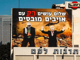 A billboard in Tel Aviv, depicting blindfolded Palestinian president Mahmoud Abbas and Hamas leader Ismail Haniyeh kneeling, February 15, 2020.