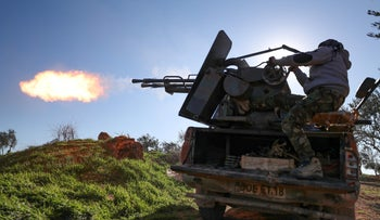 A Turkey-backed Syrian fighter fires a truck-mounted gun toward the town of Saraqeb in northwestern Syria, February 26, 2020.
