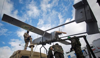 Hamas gunmen shows what they claim a locally-made drone during a rally in Gaza City, December 14, 2014.