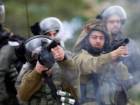 Israeli soldiers fire tear gas canisters towards Palestinian demonstrators during a protest against U.S. President Donald Trump's Mideast initiative, in Jordan Valley in the West Bank, February 25, 2020.