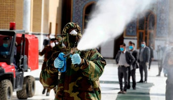 A member of the Iraqi civil defense sprays disinfectant on and around the Great Mosque of Kufa, February 27, 2020.