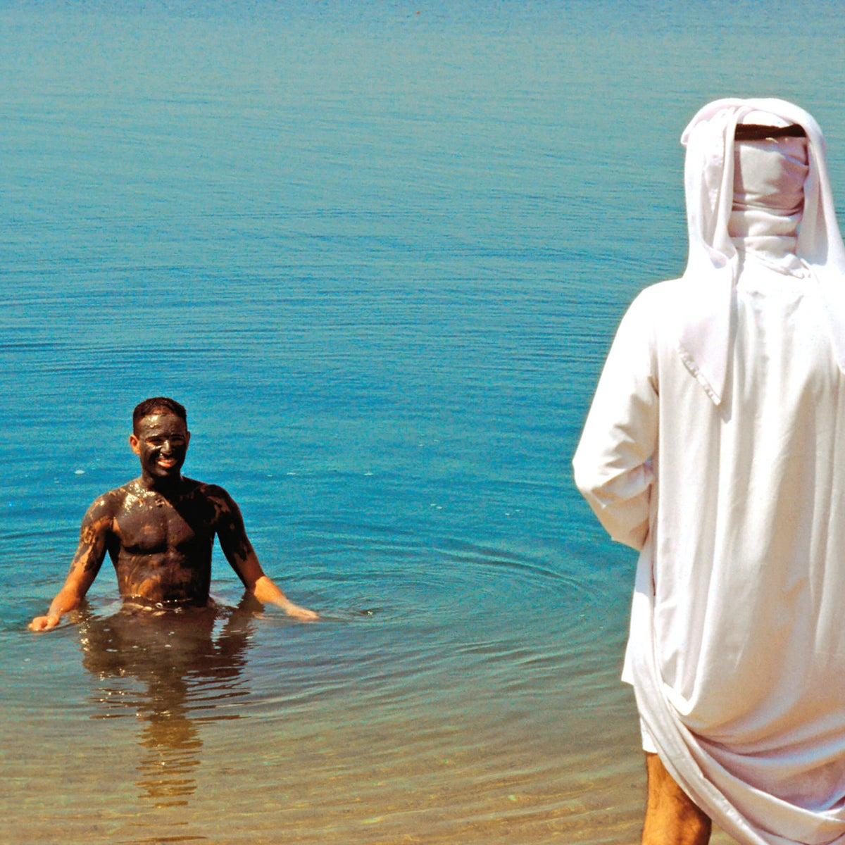 A man bathes in the Dead Sea with mud on him, a local custom.