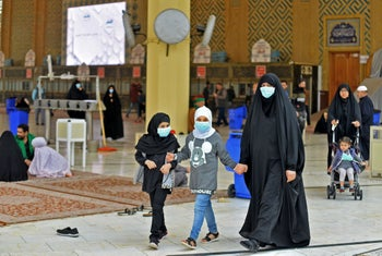 Pilgrims wearing masks walk through the courtyard of the shrine of Imam Ali on February 25, 2020 in the holy Iraqi central city of Najaf.