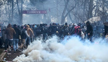 Migrants run away as Greek anti riot police officers use tears gas on the buffer zone Turkey-Greece border, at Pazarkule, in Edirne district, on February 29 , 2020.
