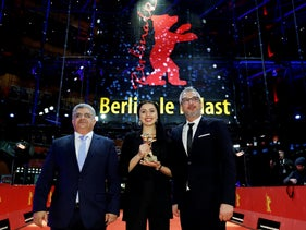 """Baran Rasoulof and producers Kaveh Farnam and Farzad Pak pose with the Golden Bear for Best Film for """"There Is No Evil"""" at the 70th Berlinale International Film Festival, February 29, 2020."""