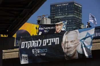 A Kahol Lavan party activist waving a flag behind an election campaign billboard showing party leader Benny Gantz, Tel Aviv, March 1, 2020.