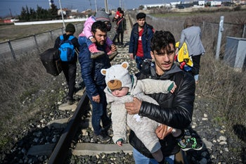 A migrant carries his baby as they walk on railways toward Meritsa river, near Edirne, to take a boat to attempt to enter Greece by crossing the river on March 1, 2020.