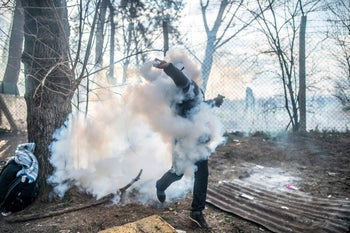 A migrant throws a gas canister back to Greek police on the buffer zone Turkey-Greece border, at Pazarkule, in Edirne district, on February 29, 2020.