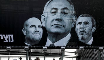People walk along a pedestrian overpass beneath an election billboard in the central Israeli city of Ramat Gan on March 1, 2020.