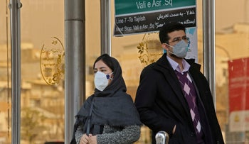 People wearing protective masks stand at a bus station in the Iranian capital Tehran on February 24, 202