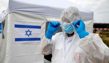 A paramedic adjusts his protective suit as he prepares outside a special polling station for voters in coronavirus quarantine in Ashkelon, Israel, March 2, 2020.