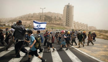 Israeli school children cross a road with an Israeli flag in the Jewish neighborhood of Har Homa, in east Jerusalem, May 10, 2010.