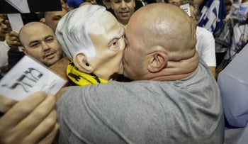 A Likud activist kisses a fellow Netanyahu supporter wearing a mask of the prime minister after Israeli election exit polls were released Monday evening.