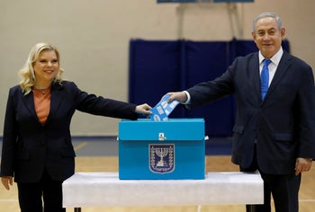 Prime Minister Benjamin Netanyahu, right, and his wife Sara Netanyahu cast their ballots during the Israeli legislative elections at a polling station in Jerusalem, Monday, March 2, 2020.