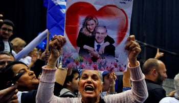 Likud supporter holding up a poster with Prime Minister Benjamin Netanyahu embraced by his wife Sara at Likud party headquarters in Tel Aviv on Monday after the polls closed.