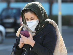 An Iranian woman wearing a protective mask checks a message on her smart phone in the Iranian capital Tehran on March 2, 2020