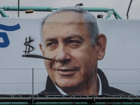 A defaced Likud campaign poster, with a picture of leader Netanyahu with a cigar in his mouth and smoke shaped like dollar signs, Jerusalem, March 2, 2020.