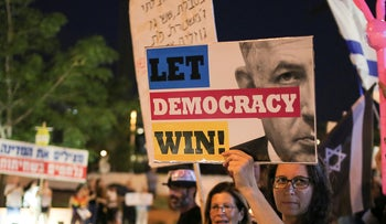 A protester holds a placard during a demonstration against Israeli Prime Minister Benjamin Netanyahu amid investigations on corruption charges, August 17, 2019.