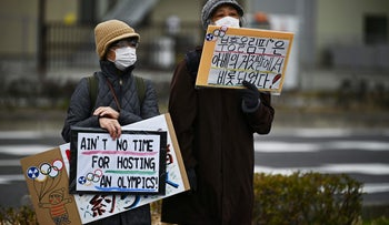 Protesters holding placards during a demonstration against the Olympics near the 'J-Village' that will host the start of the Olympic torch relay in Naraha, Fukushima prefecture, February 29, 2020.