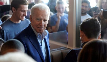 Joe Biden talks with customers as people watch through the windows at the Buttercup Diner during a campaign stop in Oakland, California, March 3, 2020.