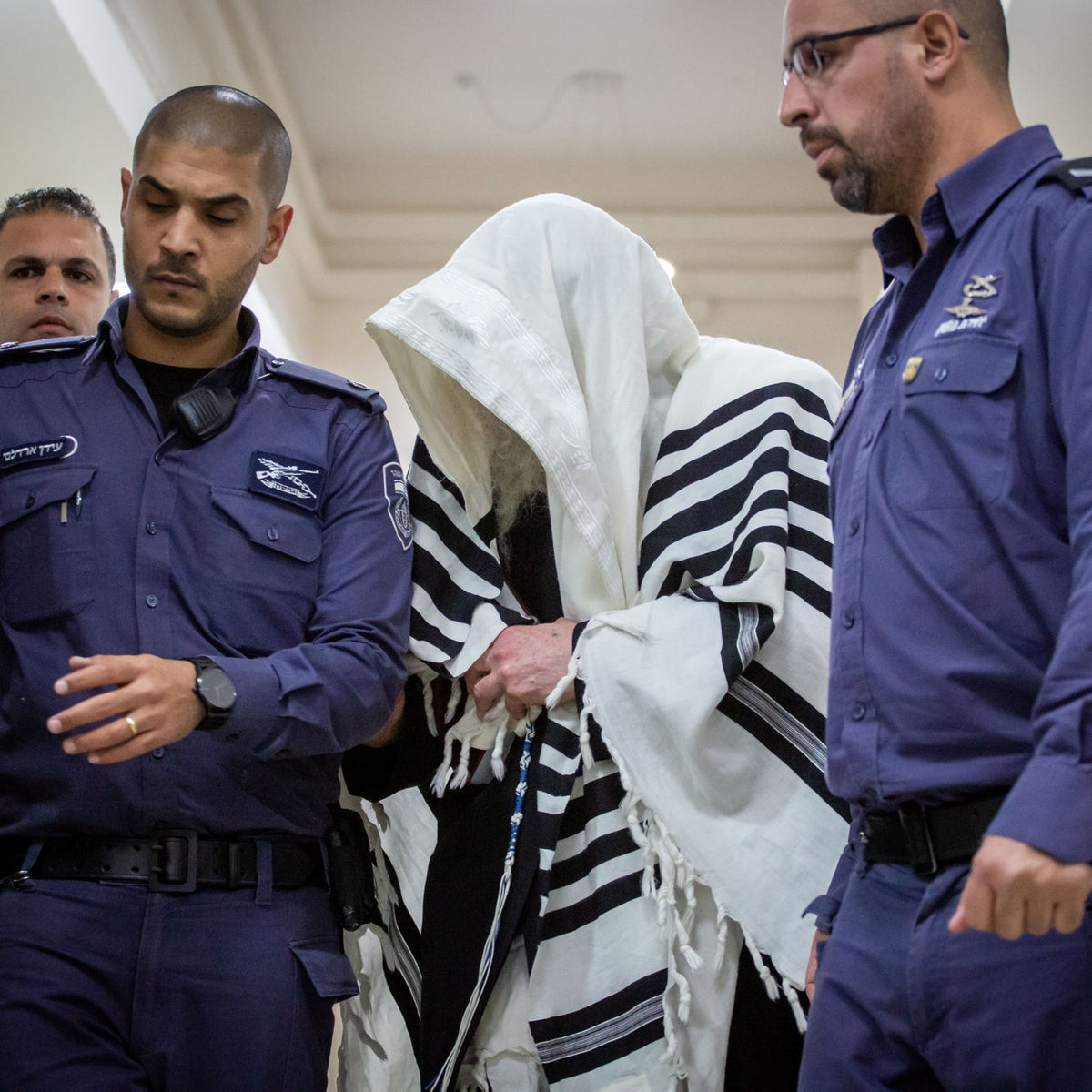 Rabbi Eliezer Berland, center, is being led into court in January 2020.