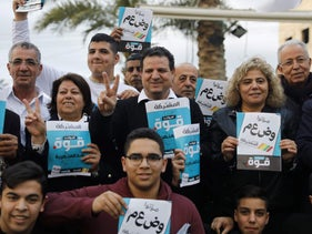 Ayman Odeh of the Joint List poses among supporters with election pamphlets during a campaign rally in Taibeh on February 21, 2020.