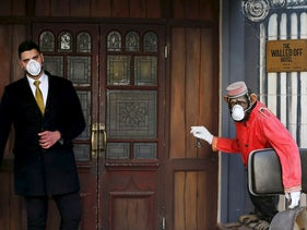 A member of staff wears a mask as a preventive measure against the coronavirus as a statue of a chimpanzee bell-boy with a mask is seen at the entrance of The Walled Off Hotel in Bethlehem, in the Israeli-occupied West Bank March 5, 2020