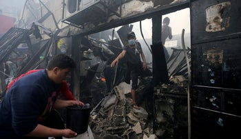 Palestinians work at the scene where a fire broke out in a market in the central Gaza Strip, March 5, 2020