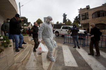 Palestinian policeman delivers supplies to the hotel staff which tested positive to coronavirus to a hotel in Bethlehem, West Bank, Friday, March 6, 2020