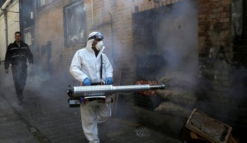 A firefighter disinfects a traditional shopping center to help prevent the spread of the new coronavirus in northern Tehran, Iran, March, 6, 2020.