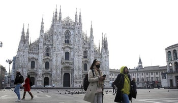 In this Sunday, Feb. 23, 2020. file photo, a woman wearing a sanitary mask walks past the Duomo gothic cathedral in Milan, Italy