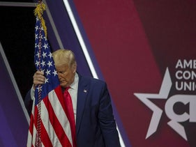 Then President Donald Trump rests his head on the flag of the United States of America at the annual Conservative Political Action Conference (CPAC)