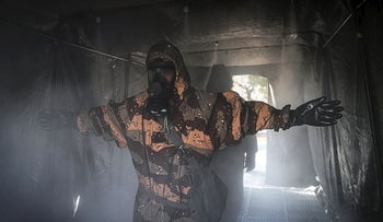 In this Sunday, March 1, 2020, photo, an Iranian army member disinfects his protective gear against the new coronavirus in Tehran, Iran