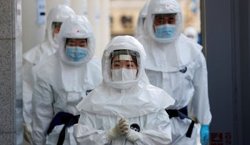 Medical workers in protective gears walk into a hospital facility to treat coronavirus patients in Daegu, South Korea, March 8, 2020.