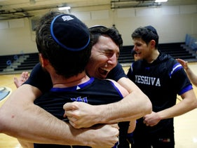 Yeshiva forward Michael Bixon hugs forward Daniel Katz, back to camera, after the team's 102-83 win over Penn State-Harrisburg in the second round of the NCAA men's Division III college basketball tournament Saturday, Baltimore, March 7, 2020,