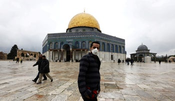 A man wears a face mask near the Dome of the Rock, in Jerusalem's Old City, March 6, 2020.