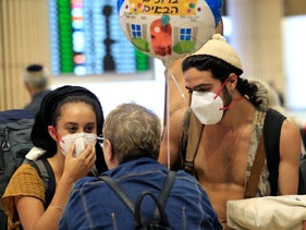 A young couple wearing protective masks are greeted upon arrival at Ben Gurion International Airport near Tel Aviv, March 4, 2020.
