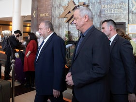 Benny Gantz, right, and Avigdor Lieberman leave a meeting in central Israel, March 9, 2020.