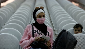 A Palestinian woman, wearing a mask as a preventive measure against coronavirus, waits in the departure hall at the Israeli-controlled Allenby Bridge crossing, in the West Bank, on March 10, 2020.