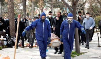 Men carry the body of lawmaker-elect Fatemeh Rahbar, who died of the virus, at Behesht-e-Zahra cemetery outside Tehran, Iran, March 8, 2020.