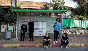 Kadri and her kids and Sha'aban and his son in a bus stop in Carmiel, March 2020.