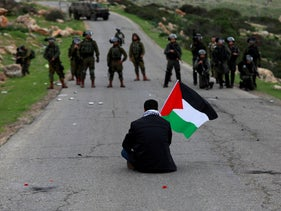 A demonstrator holding a Palestinian flag sits in front of Israeli forces during a protest in the Israeli-occupied West Bank February 25, 2020.