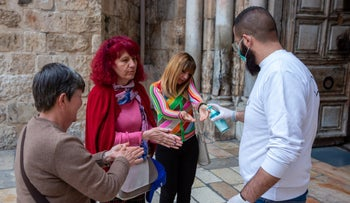 Tourists being given hand sanitizer outside the Church of the Holy Sepulchre, Jerusalem, March 10, 2020.