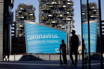 "Italians pass by a banner reading ""Coronavirus: let's stop it together,"" at the Porta Nuova business district in Milan. March 11, 2020."