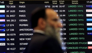 A man walks past the screen announcing arrivals at Israel's Ben Gurion airport, March 4, 2020.