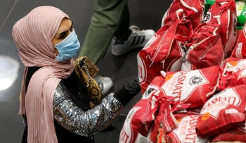 A woman wears a mask and gloves, as she checks products at a supermarket as people begin to stock up on provisions, in Beirut, Lebanon, March 11, 2020.