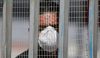 A man, wearing a mask against coronavirus infection, looks through a fence as he waits for Palestinians returning from abroad. Gaza's Rafah border crossing with Egypt. March 8, 2020