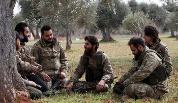 Ahmed Mansour and his comrades rest under an olive tree near Binnish, Syria February 27, 2020. Picture taken February 27, 2020